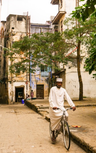 A boy biking through the heart of the Stone Town.